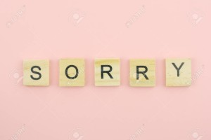 Text wooden blocks spelling the word sorry on pink background